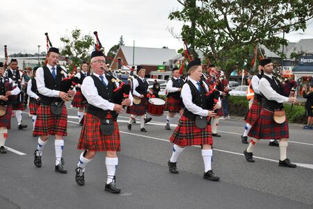 scottish band marching through the street at kumeu new zealand christmas parade