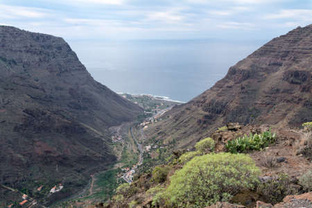depending: view into the valley floor of valle gran rey park rural gomera. Gomera is one of the most attractive canary islands, depending to spain. It is a vulcan island. you can reach gomera by taking the ferry from teneriffa. No international flights arrive here. Stock Photo