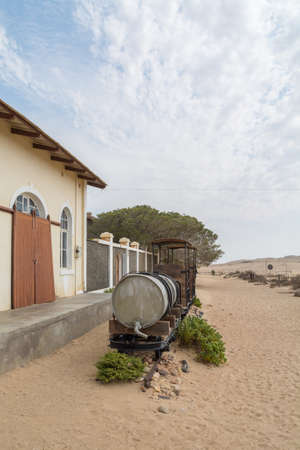 NAMIBIA, KOLMANSKOP - SEPTEMBER, 14. 2014: Ghost Town Kolmanskop, former Diamond Dagger Town in desert stripe near Luederitz. It was used from 1908 till 1930. Now its abandoned and desertificated. Train. Редакционное