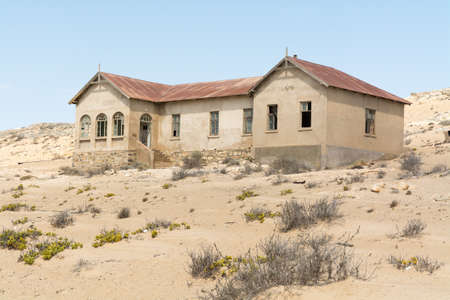 NAMIBIA, KOLMANSKOP - SEPTEMBER, 14. 2014: Ghost Town Kolmanskop, former Diamond Dagger Town in desert stripe near Luederitz. It was used from 1908 till 1930. Now its abandoned and desertificated. Physician Building.
