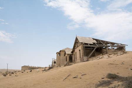 desertification: NAMIBIA, KOLMANSKOP - SEPTEMBER, 14. 2014: Ghost Town Kolmanskop, former Diamond Dagger Town in desert stripe near Luederitz. It was used from 1908 till 1930. Now its abandoned and desertificated.