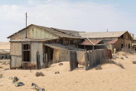 desertification: NAMIBIA, KOLMANSKOP - SEPTEMBER, 14. 2014: Ghost Town Kolmanskop, former Diamond Dagger Town in desert stripe near Luederitz. It was used from 1908 till 1930. Now its abandoned and desertificated. Ruin.