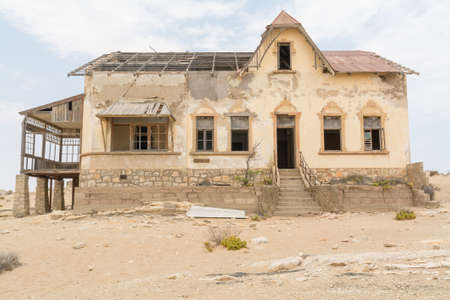 NAMIBIA, KOLMANSKOP - SEPTEMBER, 14. 2014: Ghost Town Kolmanskop, former Diamond Dagger Town in desert stripe near Luederitz. It was used from 1908 till 1930. Now its abandoned and desertificated. Accountancie Buidling.