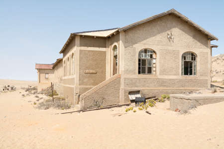 NAMIBIA, KOLMANSKOP - SEPTEMBER, 14. 2014: Ghost Town Kolmanskop, former Diamond Dagger Town in desert stripe near Luederitz. It was used from 1908 till 1930. Now its abandoned and desertificated. Hospital Building. Редакционное