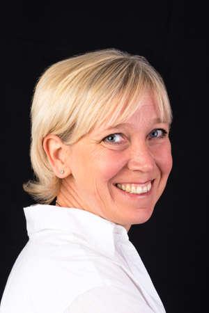 beautiful caucasian mature woman in white shirt, headshot - photograph on black background Stock Photo