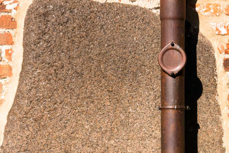 sink drain: View of a red-brick exterior wall with brown drainpipe - for background purposes