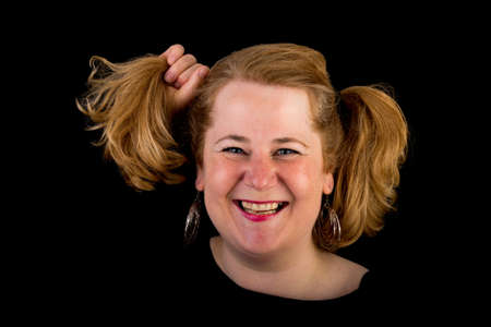 Attractive red haired lite overweight european mature woman with funny hair style - pulling her hair, studio shot on dark background Stock Photo