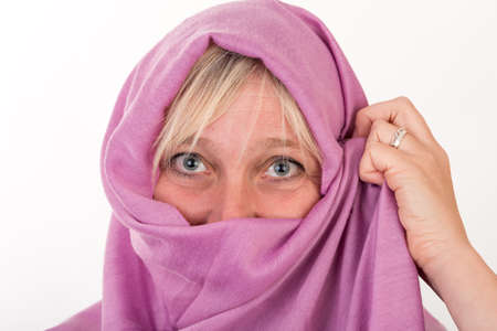 beautiful european mid aged woman hiding her face behind a shawl - studio shot on white background Stock Photo