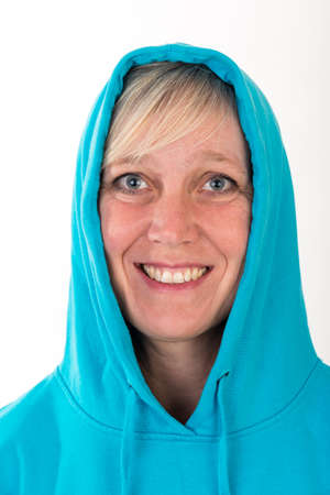 Beautiful european mid aged woman with blonde hair dressed in a light blue casual hooded jacket - studio shot in front of a white background Stock Photo