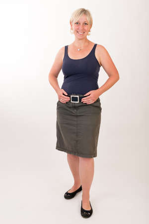 portrait of a attractive blond haired mid aged european woman wearing green skirt and blue top showing happy face - full body - studio shot on white background. Imagens