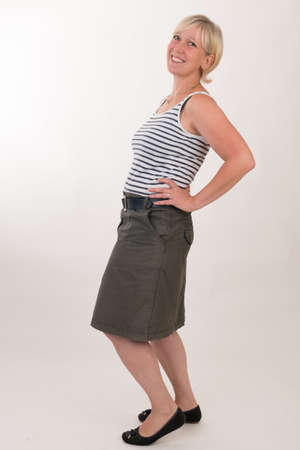 portrait of a attractive blond haired mid aged european woman wearing green skirt and blue white striped topshowing happy face - full body - studio shot on white background. Reklamní fotografie - 80831995