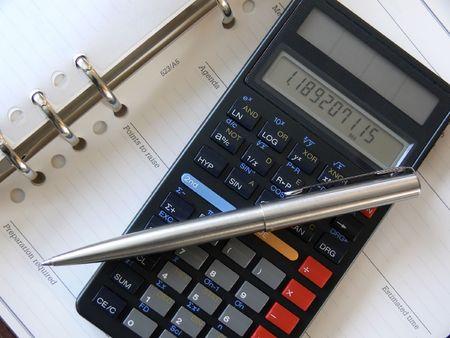 ballpoint pen lying across scientific calculator, resting on open diary