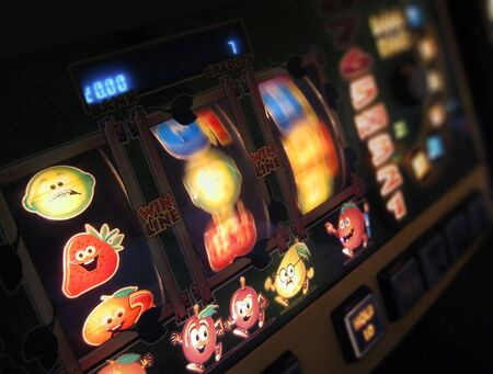 slot machine: slot machine wheels spinning, reels brightly lit, differential focus