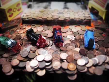 penny pusher or Penny Falls amusement machine, with prizes of toy locomotive engines Stock Photo