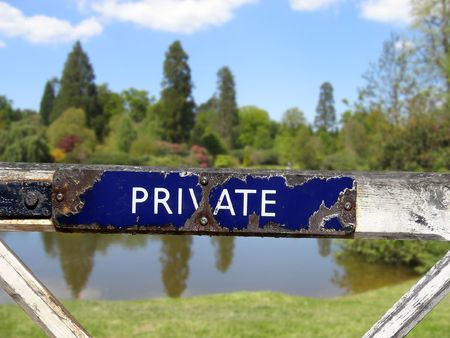corroded private sign on gate leading to beautiful lake and countryside under summer sky