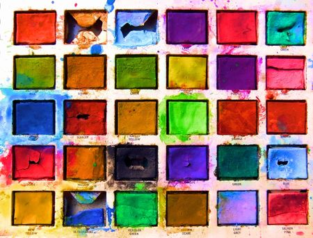closeup of childs old tin toy paintbox with the brilliant colours of childhood