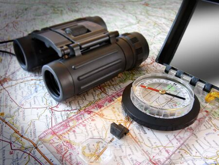 still life: hiking compass and binoculars on map (of Italy - but only occasional place name legible); differential focus