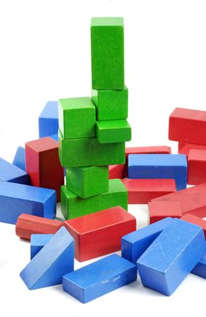 tower of green bricks rising from a random pile of red and blue vintage wooden toy building blocks; differential focus