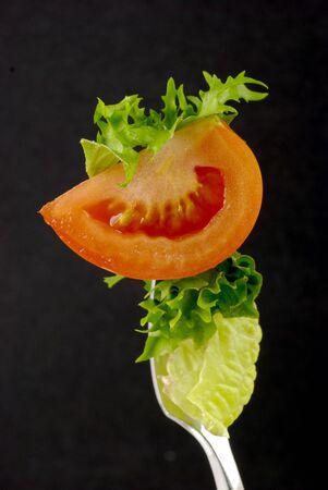 cherry-tomato and lettuce leaf impaled on fork