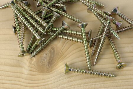 group of wood screws resting on wooden plank Stock Photo