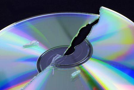 data loss -- broken CD or DVD isolated on black ground Stock Photo