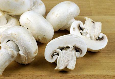 button mushrooms (Agaricus bisporus) on wooden chopping board Stock Photo