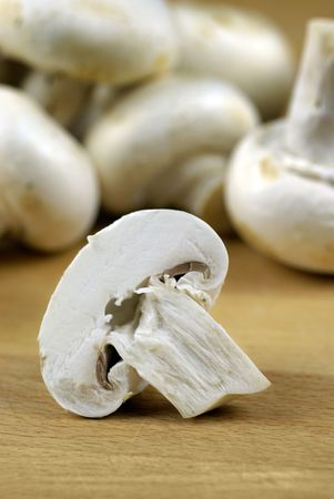 halved  half: button mushrooms (Agaricus bisporus) on wooden chopping board Stock Photo