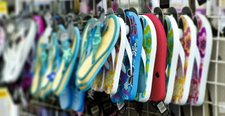 flipflop: Rack of flip-flop beach shoes (thongs); rack of colourful flip-flops for sale; strong differential focus