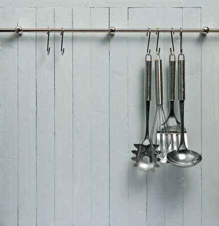 Kitchen cooking utensils on steel rack; steel spatulas etc against rustic wooden wall; good copy-space Stock Photo