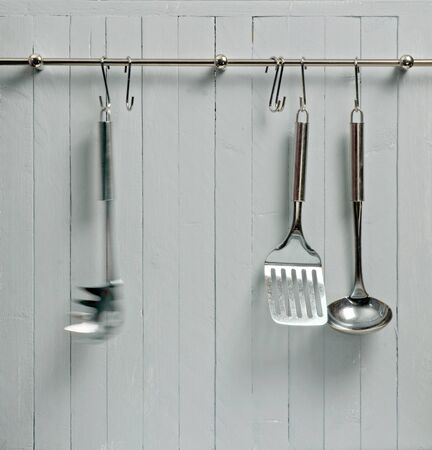 Kitchen cooking utensils on steel rack; steel spatulas etc against rustic wooden wall; motion blur on one tool; good copy-space photo