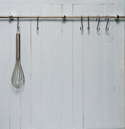 kitchen utensils: Cocina cocina utensilio en rack de acero; batidor acero contra la pared de madera r�stica; Good copy-space Foto de archivo