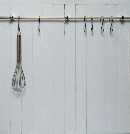 Kitchen cooking utensil on steel rack; steel whisk against rustic wooden wall; good copy-space photo