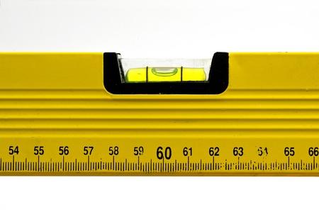 Yellow spirit level; well-used spirit level isolated against white ground