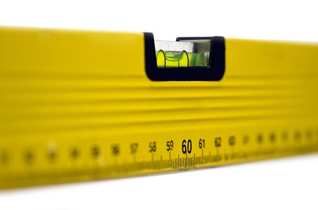 Yellow spirit level; well-used spirit level isolated against white ground; strong differential focus