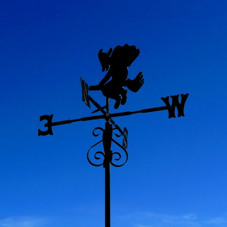 witch weather vane; silhouetted against deep blue sky