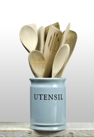 Kitchen cooking utensils; wooden spatulas etc in china storage pot; isolated on wooden shelf