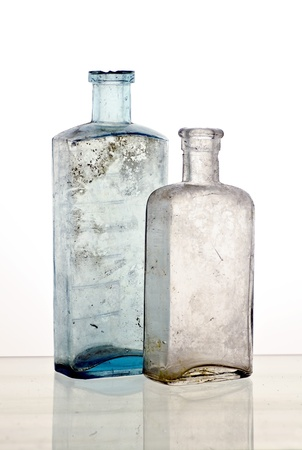 Vintage medicine bottles; two colourless poison bottle; reflections at base of image Stock Photo - 9788718