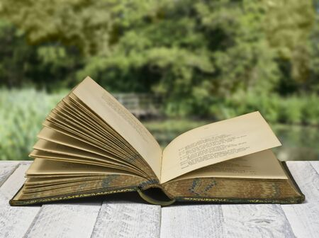 Vintage poetry book; lying on table against countryside background