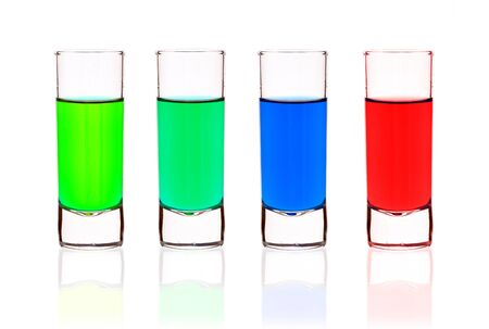 Four shot-glasses of brightly-colored cocktails - isolated on white ground Stock Photo