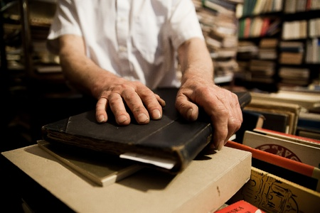Photo of man in secondhand bookshop and his hands on old books Editorial