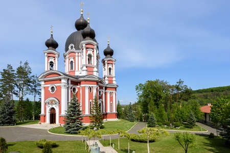 Orthodox Curchi monastery in Moldova with green trees and blue sky