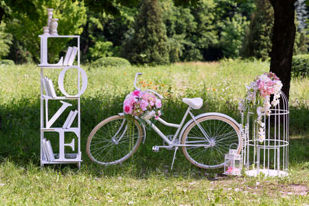 Wedding composition with love stand, a white bycicle and flowers