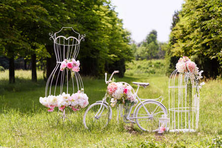 Wedding composition with love stand, a white bycicle, woman dress shaped stand and flowers