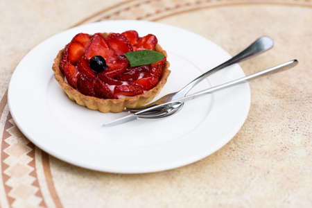 custard slice: Photo of a fruit cake with strawberries, mint and blackcurrant, on a white plate with knife and fork on a restaurant table.