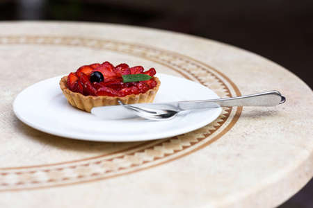 Photo of a fruit cake with strawberries, mint and blackcurrant, on a white plate with knife and fork on a restaurant table.