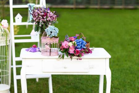 Décoration de mariage vintage avec table blanche, fleurs et cage de perroquet.