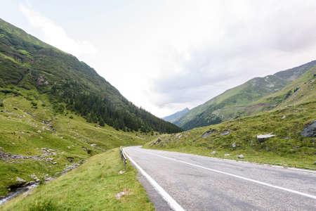 fagaras: Photo of green capra peak, a road and a small river in fagaras mountains, Romania. Stock Photo
