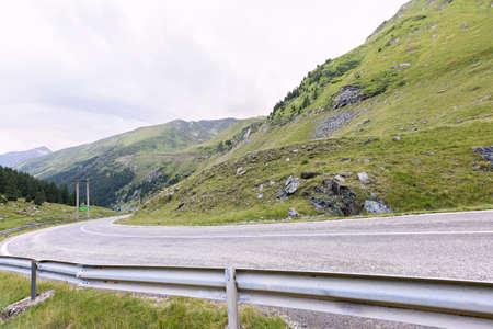 capra: Photo of green capra peak, a road and a small river in fagaras mountains, Romania. Stock Photo