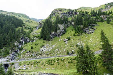 fagaras: Photo of green peaks, a small river and a road in fagaras mountains, Romania.