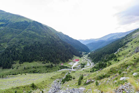 Photo of capra peak and famous winding road in fagaras mountains at sunset, Romania. Stock Photo